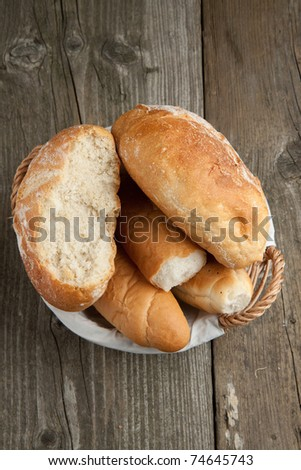 Top view on fresh bread in basket on old wooden table
