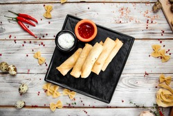 Top view on fried spring rolls with cheese filling and red sauce, horizontal