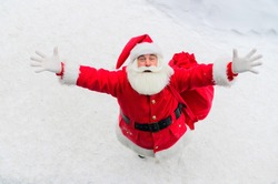Top view on friendly santa claus actively gesturing and wishing merry christmas. An elderly man in a Santa costume stands on the snow outside and wishes a happy new year.