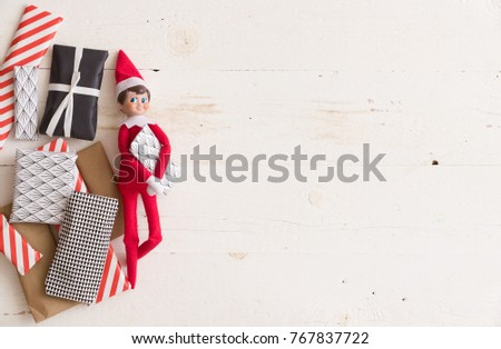 Top view on funny Christmas toy with small gifts for advent calendar on white wooden background. #767837722