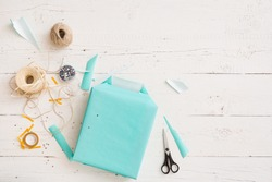 Top view on gift wrapping. Gift in paper of turquoise color. Gift ribbons, twine, scissors and gift on a white wooden table. Preparation for the holiday. Christmas, birthday, etc.