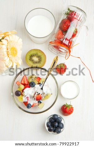 Top view on glass bowl of fruit salad with fresh strawberries, blueberries, kiwi and whipped cream, with bunch of flowers and glass jar of strawberries on white table