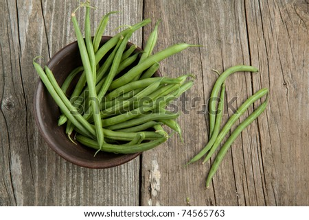 Top view on green beans in ceramic bowl on old wooden table