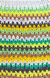 Top view on hand-knitted  striped pattern of green, brown and yellow colors. Beautiful warm handmade knee socks. Knitwear background. Flat lay, close-up, top view