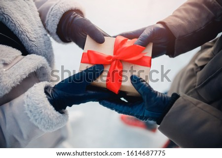 Top view on hands in winter gloves, lovers give gift to craft boxes with red bow. Christmas romantic surprises.
