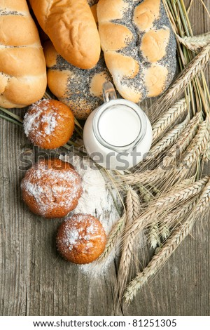Top view on lot of bread and cakes with jug of milk and spikes of rye