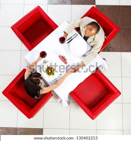 Top view on middle aged man and woman holding hands in a restaurant