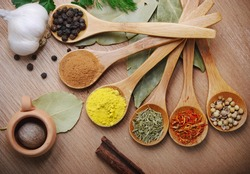 Top view on mixed dry colorful spices in wooden spoons on rustic table. Food and cooking ingredients concept. pepper, chili, curry, saffron and garlic on wooden background.