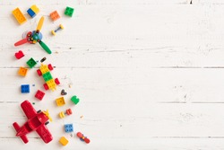 Top view on multicolor toy bricks on white wooden background. Children toys on the table.