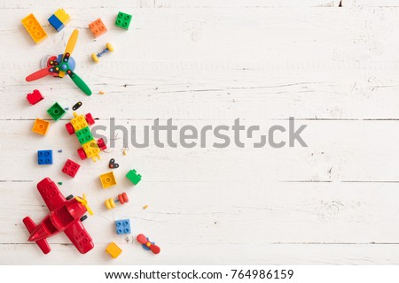 Top view on multicolor toy bricks on white wooden background. Children toys on the table. #764986159