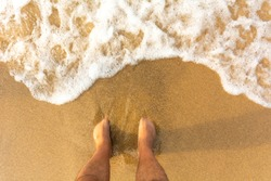 Top view on naked feet in sand on beach copy space - Foaming sea texture background ocean while standing barefoot fine sand beach - Point of view on legs in sand with sea foam ocean summer background