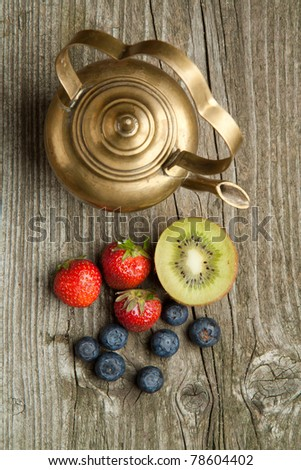 Top view on old vintage teapot with fresh strawberries, blueberries and kiwi on old wooden table