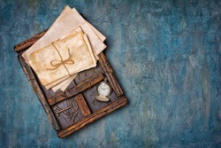 Top view on old yellowed bunch of letters with retro keys and silver pocket watch in vintage wooden box on blue grunge concrete background with copy space