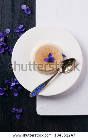 Top view on plate with caramel pannacotta served with violet flowers over black and white table