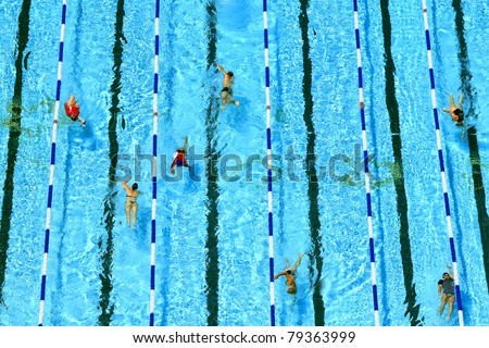 Top view on pool with blue water and floating people