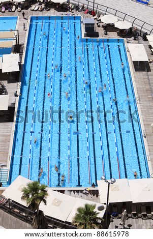 Top view on pool with blue water and floating people - stock photo