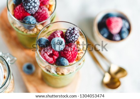 Top view on portions of chia pudding with matcha tea, organic granola, frozen berries in glasses. The concept of healthy vegan food.