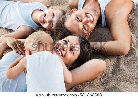 Top view on  positive  parents with kids relaxing on sandy beach on sunny day #561666508