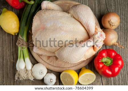 Top view on raw chicken, onion, garlic, red paprika and lemon on old wooden table - stock photo