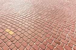Top view on red paving stone road. Old pavement of granite texture. Street cobblestone sidewalk. Abstract background for design.