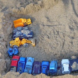 Top View On Sea Beach With Kids Toys. Sand Castle Or Fort With Many Colorful Plastic Car and Trucks On Summer Sea Coast Overhead View. Abstract Background.