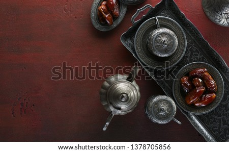 Top view on silver plate with date fruits and coffee cups on the dark red wooden background. Ramadan background. Ramadan kareem.