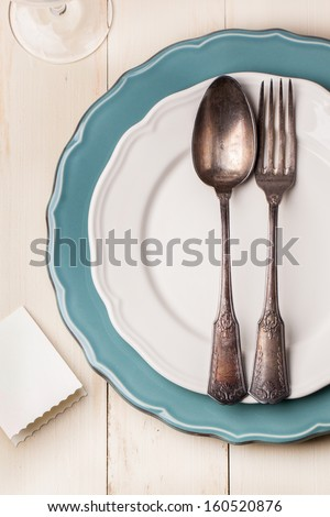 Top view on table setting with vintage silverware on white and turquoise plates with blank guest card on white wooden table