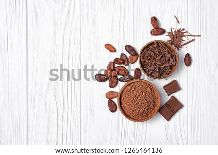 Top view on tasty chocolate bars with cocoa beans and bowl of chocolate chips and cacao powder as ingredients for confectionery on white wooden background with copy space