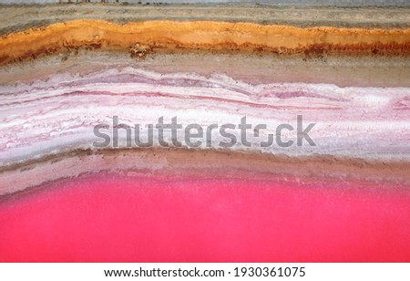 Top view on the cliff of the shore washed by the water of the pink lake. The salt deposited on the shore has a pink tinge. Stockfoto ©