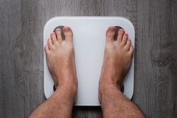 Top view on the feet of a barefoot man standing on a smart scale. White smart weights with empty balance standing on a gray wooden floor. Conceptual photo of weight loss.