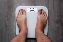 Top view on the feet of a barefoot man standing on smart scales on whose balance a sad face appears. Conceptual photo of weight loss.
