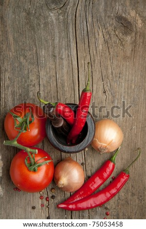 Top view on tomato, onions and red hot chili peppers in old mortar on old wooden table