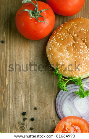 Top view on tow fresh tomatoes, burger's bun and sliced onion on wooden table as background