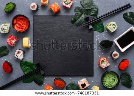 Top view on traditional japanese empty square black slate plate framed with sushi, ginger, soy, wasabi bowls, green leaves and chopsticks on rustic grey backround copy space