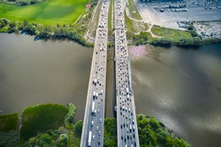 Top view on traffic on the straight bridge over water. Parallel separate roads.