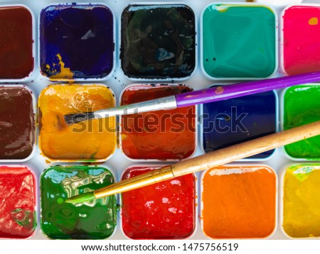 Top view on two paintbrushes lying on watercolor pallet #1475756519