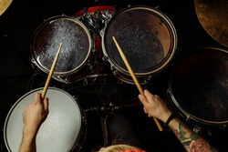 top view on unrecognizable caucasian drummer playing on drum kit. young professional drum player kick drum plate. man enjoy music, use sticks