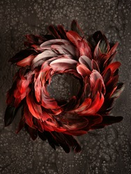 Top view on vintage black, red, maroon, and flaming orange feather wreath. Flat lay on warm dark textured background. Dark luxury design. Reach, bold Autumn or Winter color shades.