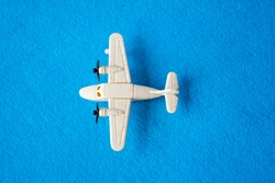 Top view on white plane with two propellers. Children scale models of airplane. Small aircraft bauble with engines on rounded wings. Plastic playthings isolated on blue background