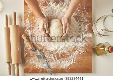 Top view on white table with isolated wooden board with knife, two rolling pins, bottle olive oil, transparent jar with flour Woman hands hold prepared dough for pasta or dumplings