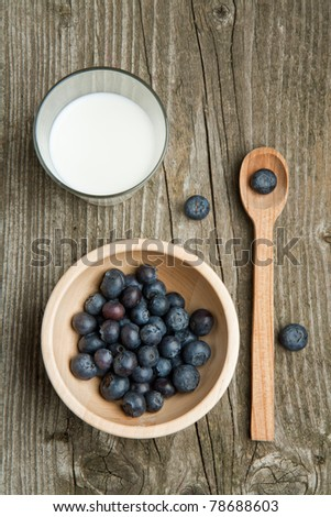 Top view on wooden bowl of fresh blueberries, wooden spoon and glass of milk on old wooden table - stock photo