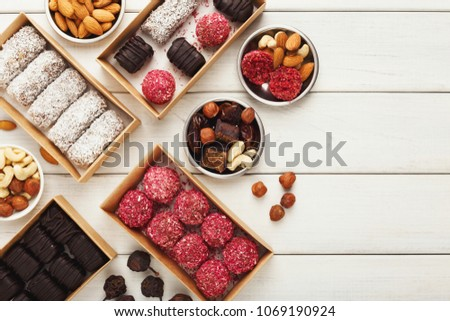 Top view on wooden table with variety of healthy raw vegan candies, almonds, hazelnuts, dates. Fitness dessert and eating right concept, copy space