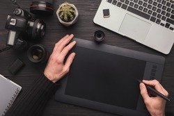 Top view on workplace of photographer. Creative designer hands working graphic tablet, photographic equipment on table