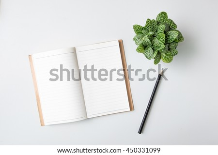 Top view open notebook, pencil and plant potted on white desk background