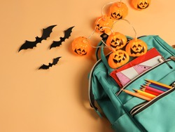 Top view or flat lay  of backpack with school supplies, Halloween pumpkin lights and black paper bats  on orange background. Education and Halloween concept.