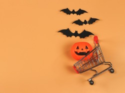 Top view or flat lay of  Halloween pumpkin on shopping cart  with black paper bats on orange background with copy space. Halloween holiday concept.