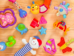 top view or flat lay on colorful toys on light wooden background. Warm vintage filter