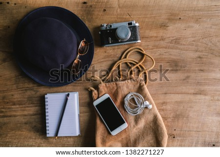 Top view or Flat lay the accessories to travel with women / lady or female clothing handbag and hat also sunglasses with item technology.Essential items for traveler mobile phone on table background