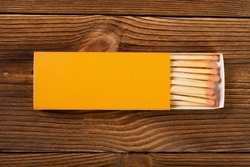 top view orange color matchbox with orange match sticks on a wood table
