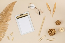 Top view over desktop with notepad, glasses and golden accessories. Home office, business woman, stylish workinf space concept. Flat lay, mockup